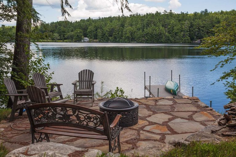 Stone patio by lake with dock