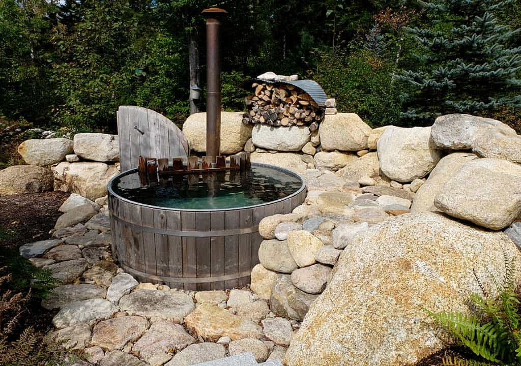 Wood fired hot tub with stone surround in New Hampshire